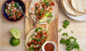 Top view of Fish Tacos with Salmon and Pico de Gallo on a wooden board