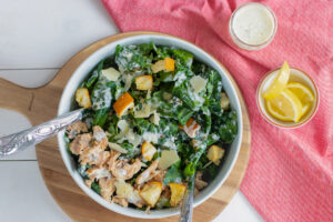 A bowl of Salmon Kale Caesar Salad