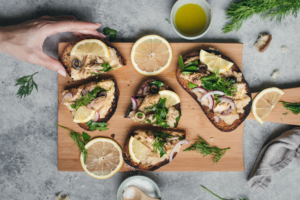 Mackerel And Refried Butter Beans Tartines on a wooden board with lemon slices
